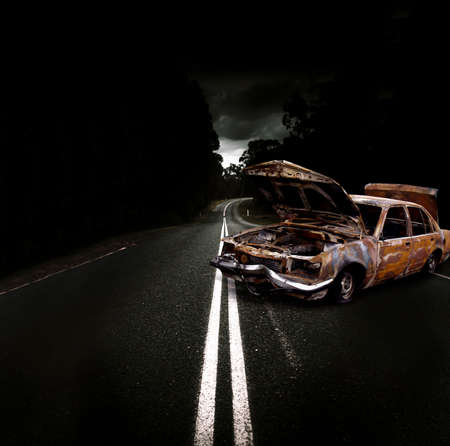 used: Smashed Up And Wrecked Car With Deflated Tyres, Missing Headlights And Dented Front Bumper Bar Parked In The Middle Of A Dark Highway Street