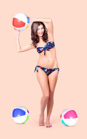 togs: Beautiful woman in full holding beach ball while playing summer sport in a bikini