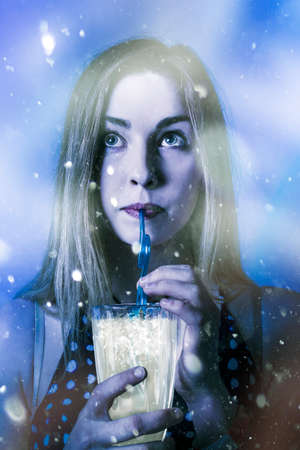 icey: Creative photo on a frozen cold winter woman drinking ice cold drink outside in falling snow. Iced beverages Stock Photo
