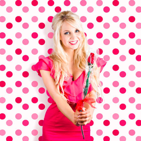 heartfelt: Romantic girlfriend with heartfelt expression receiving red rose from valentine. Pink Polka-dot background Stock Photo
