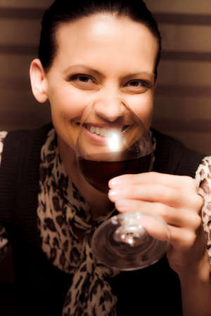 tastes: Smiling Person Sipping And Tasting Red Cabernet Merlot Wine Inside A Winery In A Taste Testing Conceptual Stock Photo