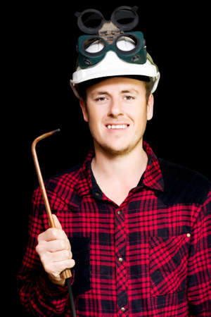 acetylene: Confident smiling young panel beater wearing a safety helmet and goggles and holding an welding torch in hand on a black studio background