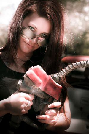 re fuel: Transport Industry Image Of A Woman Standing Outdoor At A Gas Service Station Holding A Petrol Fuel Pump Ready To Refuel Her Car With Gasoline