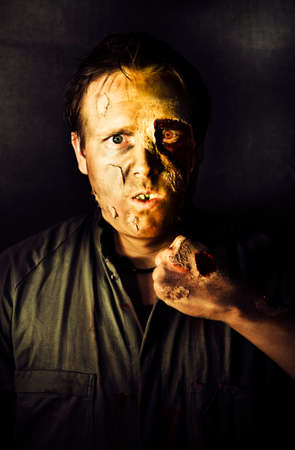 putrefy: Dark Studio Portrait Of A Rotten And Mangled Zombie Raising A Clench Fist With A Deadly Intense Gaze During A Fight Of The Living Dead Stock Photo