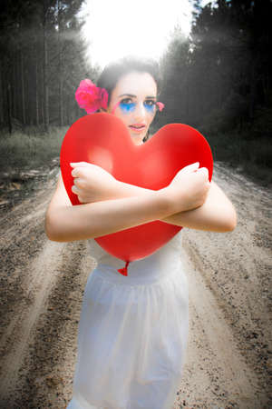 longing: Cupid The Angel Of Romance, Clinging, Clutching And Hugging A Large Red Love Heart Balloon On A Outback Dirt Road In A Depiction Of Hope And Longing