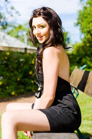 falda: Sonriente Mujer Feliz En verano brillante amarillo maquillaje que se relaja en un asiento de madera en un campo verde Or Park Llevaba Un Vestido Negro 1950 En una foto de época de verano Foto de archivo