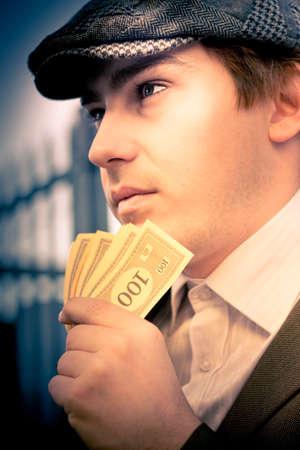 visage profil: Profil Visage Portrait Of A Vintage Man Holding A Fan Of Money To Head Alors Regarder ailleurs dans une expression de la pensée et la considération à une décision financière