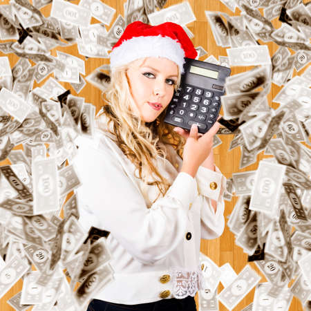 christmas budget: Christmas Woman In Santa Hat Holding Dollars Calculator Underneath Falling Banknotes In A Financial Cost Of Christmas Concept
