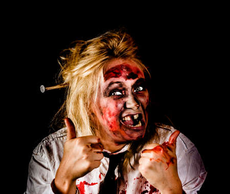 undead: Undead business zombie giving a Halloween thumbs up to negative copyspace, isolated on a black background.