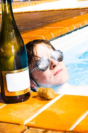 luxuries: Handsome young man with wet hair and sunglasses lounging up to his neck in the water of his sparkling pool alongside an open champagne bottle and cork as he savours the luxuries of his success