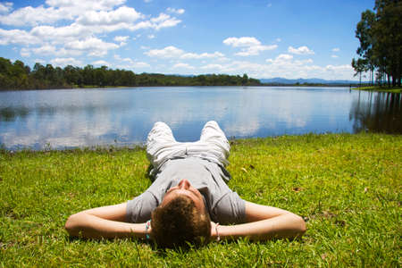 bloke: Lying Down On His Back With His Hands Behind His Neck A Young Mans Unwinds To The Sounds Of Nature
