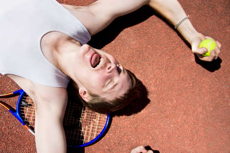 lays down: Cheerful Tennis Player Holds A Ball While Laying On His Back In A Winning Expression