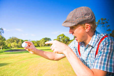 golfing: Angry Golf Sees A Sports Man Screaming Out In A Fit Of Rage On A Golf Course While Pointing At His Golf Ball After A Unsuccessful Golfing Game