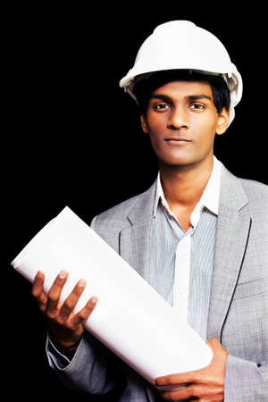 superintendent: Proud young ethnic architectural student or engineer in a hard hat and smart grey suit holds a rolled up blueprint with the design of the building they are constructing as he sets out on an inspection