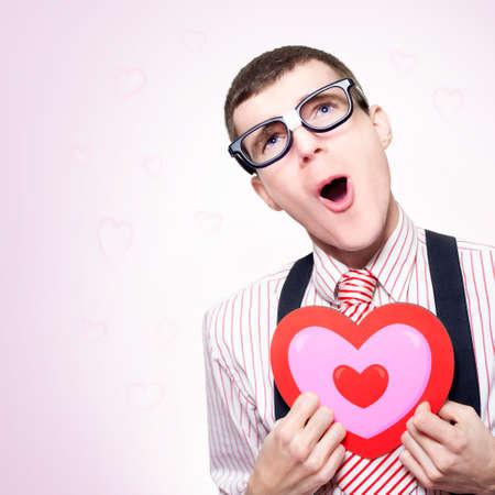 saint valentin coeur: Dr�le Portrait Of A Nerd romantique r�vant d'un long amour perdu son C?ur Dorky encore mal car, en forme de coeur Fond rose Banque d'images