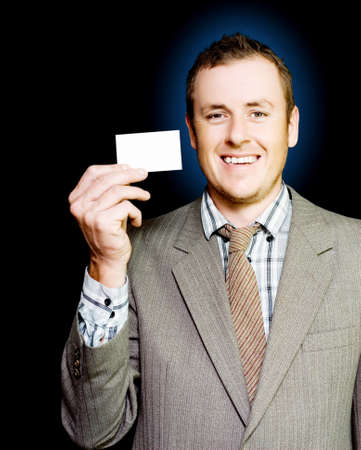 he is public: Young enthusiastic organised businessman holding up his blank busines card for attention as he strives to get his name , brand and style before the public eye in a branding concept