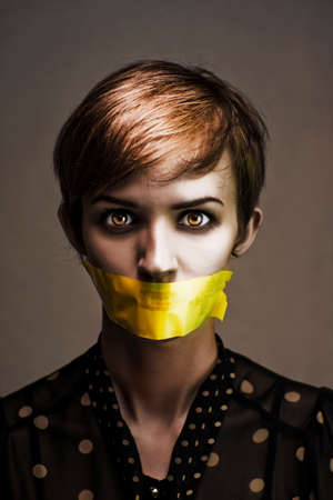 oppressed: Dark Headshot Of A Distressed And Oppressed Woman Bound And Gagged In Silence With Yellow Masking Tape Covering Her Mouth In A Speak No Evil Conceptual