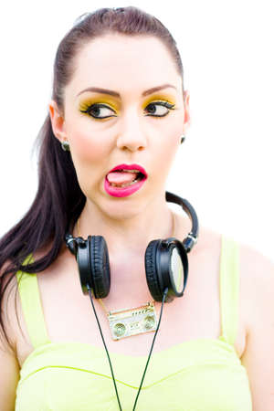 sticking: Bad Taste In Music Concept Sees A Woman Wearing Retro Technology Head Phones Poking Out Her Tongue In A Distasteful Disgusted And Offensive Expression