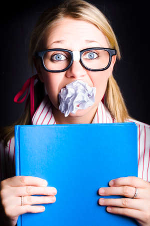 traumatised: Blue Revision Book Held Tightly In The Hands Of A Terrified And Traumatised Nerd Standing In Silence With Mouthful Of Scrunched Up Study Notes When Cramming Before Exams Stock Photo