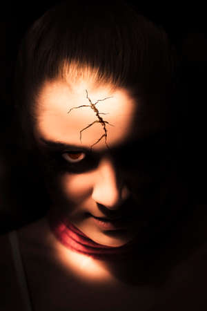 being: Focus On The Cracked And Broken Face Of An Evil And Frightening Doll Peering From The Shadows Of Darkness During Halloween In A Scary Terror Portrait