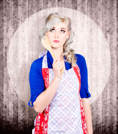 vintage kitchen: Portrait of young pinup housewife thinking what to cook in vintage kitchen with utensils Stock Photo