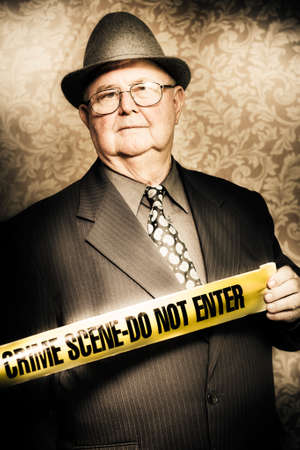 crime scene: Artistically aged portrait of an astute fifties crime investigator with a stoical expression watching carefully for any clues or odd behaviour as he unwinds the yellow tape at a fresh crime scene
