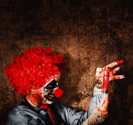 sinister: Evil halloween clown with big scary needle performing sinister healthcare practise on dark grunge background Stock Photo