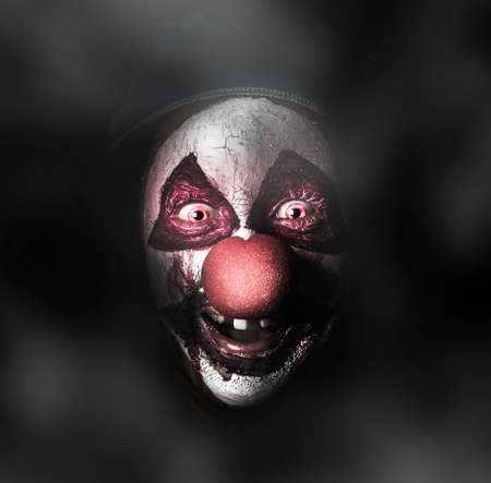 Dark carnival portrait on the face of an evil clown with a scary joker smile laughing in the black darkness. The Bogyman Stock Photo