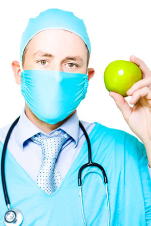 keeps: A surgeon in a mask and gown wearing a stethoscope holds up a fresh crisp green apple to demonstrate that by eating a healthy diet there is truth in the idiom Apple a day keeps the doctor away