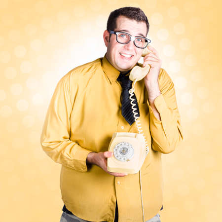 important phone call: Frightened male staff member talking with look of uncertainty on retro turn-dial telephone. Important phone call concept