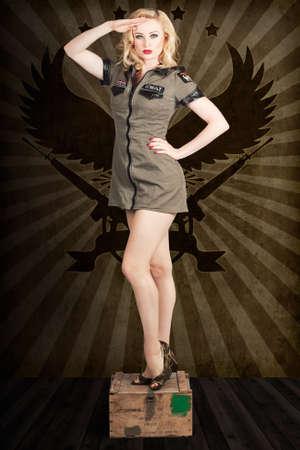 donna sexy: Bionda attraente ragazza pin-up esercito affrontando un comando con un saluto generale, in piedi sulla scatola di munizioni militari