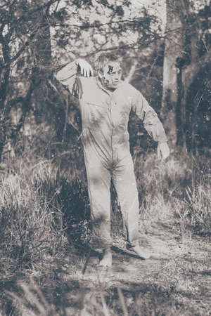 stumbling: Vintage black and white horror photograph of a walking dead zombie wearing workers overalls starting a wave of terror when stumbling through country bushland