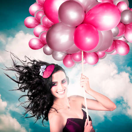 horse racing: Beautiful Smiling Australian Girl Flying High Wearing Headpiece With Balloons In A Depiction Of The Fashion Of The Field During The Melbourne Cup Spring Carnival Horse Racing Festival
