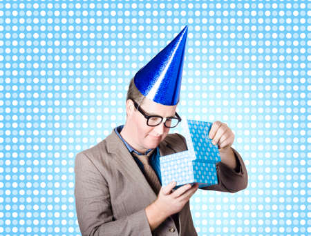 surprise party: Comical photograph of a nerdy business man wearing extra large party hat opening surprise present on blue polka-dot background. Rewards Stock Photo
