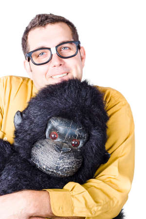goofy: Goofy, smiling man in yellow shirt holding the head of a gorilla costume Stock Photo