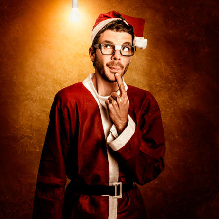 quirky: Quirky portrait of a nerd santa helper thinking of a christmas idea underneath illuminated light bulb. Clever xmas thoughts