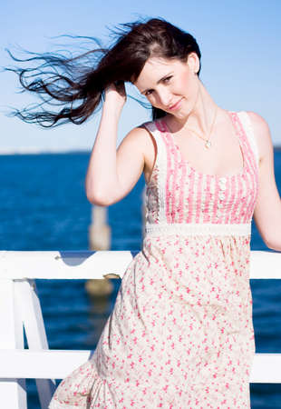 windblown: A Woman Stands Outdoor While Her Hair Blows Around In The Summer Breeze