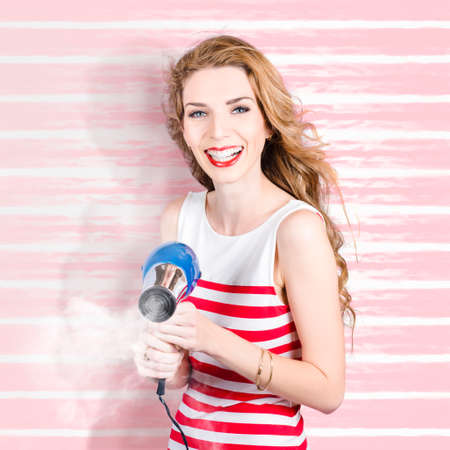 mirth: Smiling beauty hair stylist holding steaming hairdryer on salon style background. If looks could kill