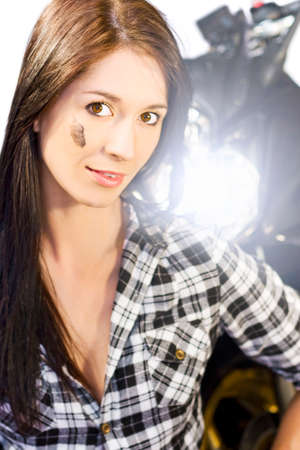 facing on camera: Female Motorcyclist Concept. Attractive young brunette woman standing facing camera with the bright headlight of a motorcycle shining over her left shoulder Stock Photo