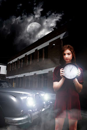 dimly: Woman Holding Clock Outside A Building Next To A Parked Car At Night Under Moonlight Stock Photo