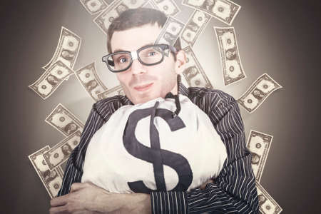 stingy: Smiling nerd businessman holding a bag full of money beneath falling US dollar notes in a depiction of smart financial gains