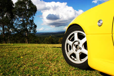 alloys: Travel Getaway Concept With A Bright Race Car Stationed On A Grassy Lookout Copy Space On Image Left Stock Photo