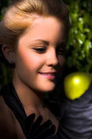 granny smith apple: Closeup Portrait Of A Beautiful, Smiling Young Woman In Black Vintage Clothes By A Tree, Holding A Granny Smith Apple In Her Black Gloved Hand