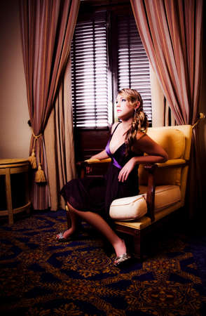 fascination: Beautiful Woman In Gorgeous Fashion Watching Movie In A Stylish Hotel Room With Discomfort, Anxiety And  Fascination In A Edge Of Your Seat Entertainment Concept Stock Photo