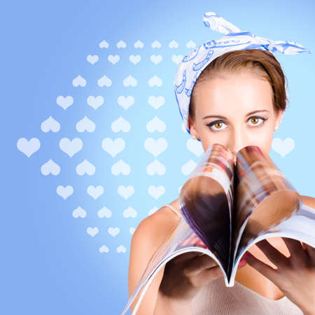 female magazine: Tabloid female reading the weekly gossip column in a womens lifestyle publication folded in a heart shape. Magazine love Stock Photo