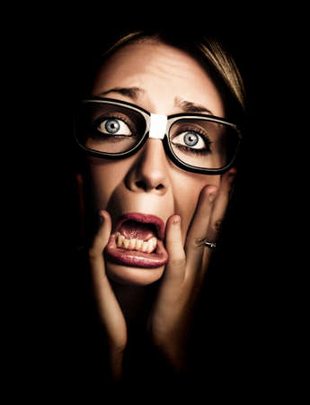 expressive face: Dark Photograph On The Scared Face Of A Business Person Wearing Eye Glasses In A Depiction Of Stress And Fear