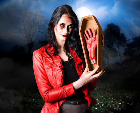 terrifying: Concept photograph of a female grave robber in terrifying makeup stealing human limbs and body parts