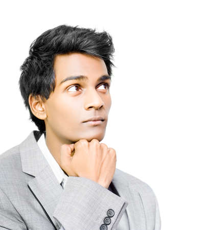 musing: Young handsome Asian businessman in deep contemplation with his chin resting on his hand as he mulls over important buiness decisions isolated on white Stock Photo