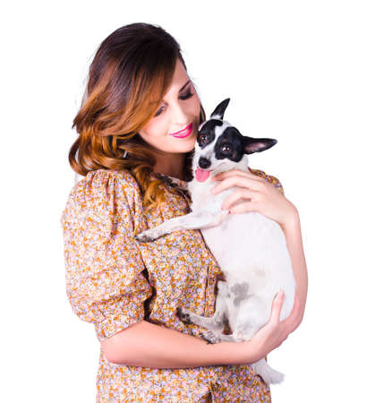 camaraderie: Attractive young woman giving her black and white pet dog a hug on white background Stock Photo