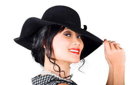 tantalising: Magnificent woman with smile holding the tip of a fashionable sunhat. Stylish hats